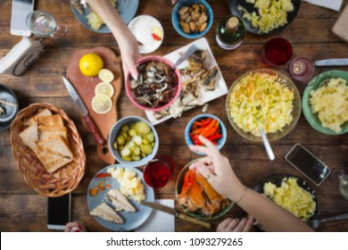 background blur. background blurred image of dinner table with different food. Easter, Christmas, Birthday, Thanksgiving. Joint toast and blow with a glass of salute in honor of the holiday. top view