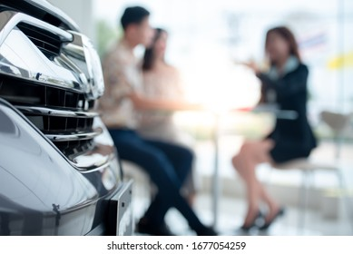 Background blur Couples are happy to buy a new car in the showroom and enter into a Buy a new car a car dealer. The concept of car buying and the concept of success