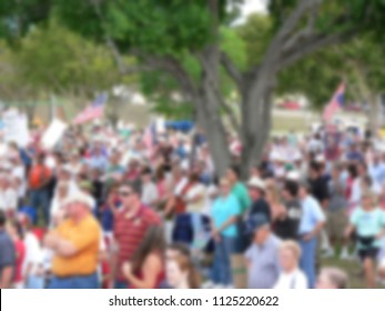 Background blur of a crowd of people in the United States. The crowd has assembled to rally for political reasons. There are signs and flags. Good for any election season.