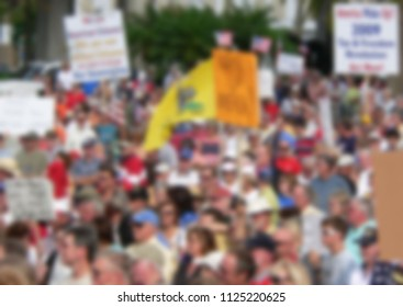 Background blur of a crowd of people in the United States. The crowd has assembled to rally for political reasons. There are signs and flags. Good for election season with message for Midterm 2018
