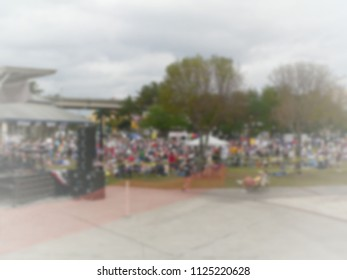 Background blur of a crowd of people in the United States. The crowd has assembled to rally for political reasons. There are signs and flags. Good for election season. White vignette applied
