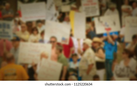 Background blur of a crowd of people in the United States. The crowd has assembled to rally for political reasons. There are signs and flags. Good for election season with vintage filters applied