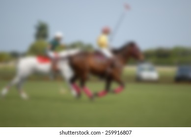 Background blur of equestrian polo players competing. The horses are visibly in action. The polo field is green grass. Horses are brown and white. Sense of speed and power is concept.