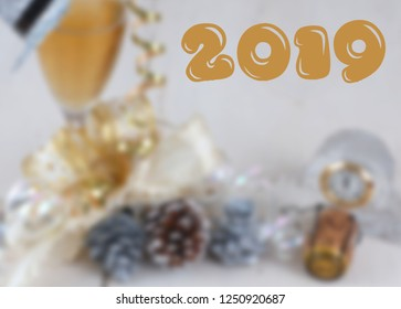 Background blur for New Year's Eve with champagne glass, clock showing almost midnight, sparkly top hat, curly ribbons and a champagne cork on wooden table. 2019 text is added.