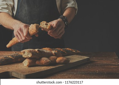 Background blur. On the background of an old brown wooden table Baker man holds halves of baguettes in his hands.pshape on a wooden board.