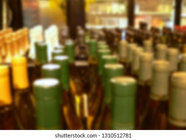 Background blur of retail setting - wine bottles lined up with a cooler in the background. Warm tones.