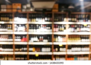 Background blur of wine shelf rack at retail supermarket store