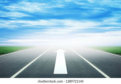 Background of blurred asphalt road, clear blue sky with clouds. Sunlit skyline