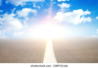 Background of blurred asphalt road, clear blue sky with clouds. Sunlit skyline