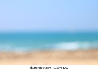 background of blurred beach and sea waves with bokeh sunset light