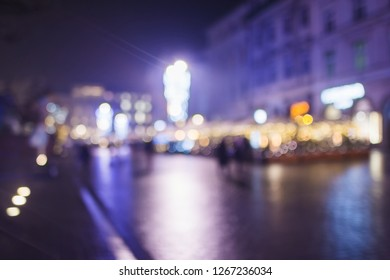 Background. In bokeh, evening city, Christmas trees, lamps, lights and ornaments. Tree alley in background. Christmas atmosphere for markets, city centers. People.