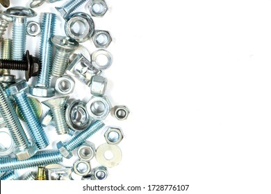 Background of bolts and nuts on a white surface with copy space.