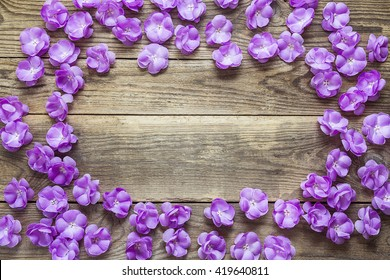 Background with a border of violet flowers on old wooden desks. Place for text. Top view with copy space