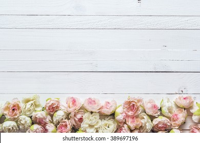 Background with border of white and pink small roses on painted wooden planks. Place for text.