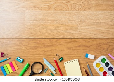 Background with bottom border made of stationery, school supplies on wooden table. Education, studying and back to school concept. Child desk top view, copy space, flat lay composition.
