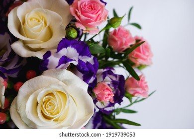 Background. Bouquet of flowers close-up on a white background. White and pink roses, blue-white eustoma. Place for text.