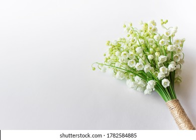Background with bouquet of lilies of valley wrapped with packthread. Photo with copy blank space.