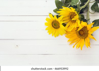 Background with a bouquet of yellow sunflowers on a white painted wooden planks. Space for text.