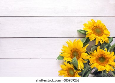 Background with a bouquet of yellow sunflowers on  white painted wooden planks. Space for text. Top view.
