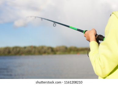 Background with a boy fisherman holding rod and weed in the background. Fishing reel visible. Setup for a peaceful catching of trench, crucian, bremes or other fish