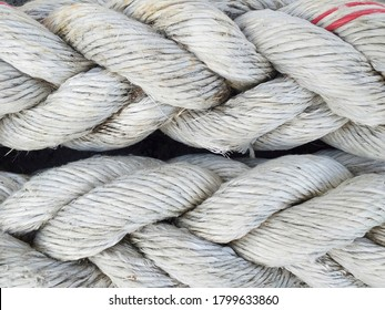 Background of braided old thick ropes. Sturdy fishing ropes to tie up the boat. Close up. Detail of a used Trawler white fishing net.