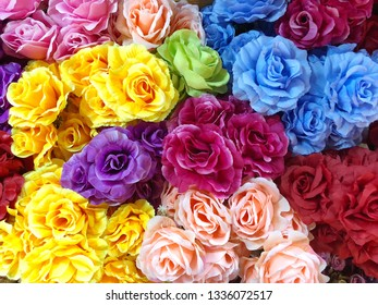 Background of bright colorful artificial roses flowers. Close up.