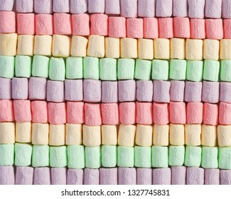 Background from bright multicolor mini marshmallow. Rows of sweet zephyr. Fon from marshmallows close up.