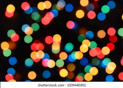Background of bright multicolored lights on a dark background. Defocused ligths.