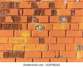 Background, bright orange brick wall. Weathered brickwork texture. Horizontal brickwork