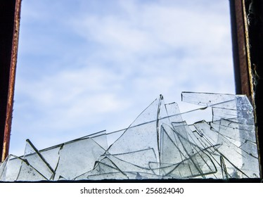 background of broken debris glass in window wooden frame backdrop against blue sky with clouds