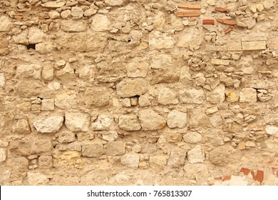 Background of brown, Beige and Gray Stones. The Old Wall of Stones. Ancient Ruins. Beige Background of Stones. Old Wall of Stones for Background, Design and Template. The island of Sicily, Italy.