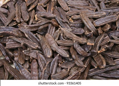 background of brown carob for sale in a market stall