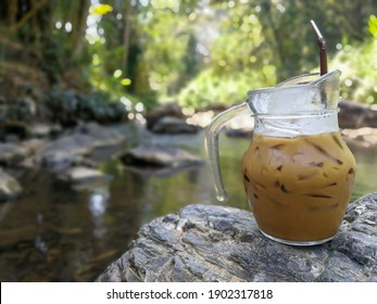 Background of brown coffee with ice on good texture rock beside stream in the forest . Peaceful and relax time