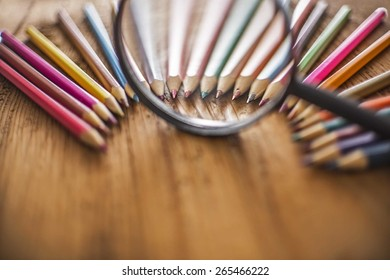 background of bunch of pencil under magnifying glass on wood table Idea of concentration and attraction to nucleus center circle radius unity concept of leadership, community, team focused on one goal