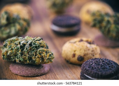 Background with cannabis nugs over infused chocolate chips cookies - medical marijuana edibles concept