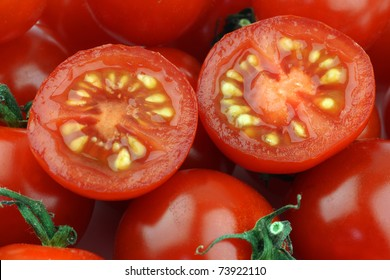 background of cherry tomatoes and a cut one with seeds visible