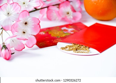 Background for chinese new year with blossom cherry flower, orange,red envelope with gold necklace put inside on white background, Chinese festival celebrates of a new year on chinese calendar.