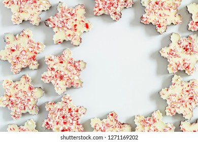 Background of chocolate peppermint bark snowflakes arranged in a circle with blank space for text