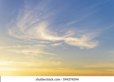 Background of cirrus clouds on the blue sky at golden sunset