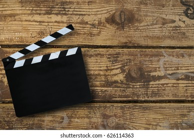 Background of a clapper board on old wooden table. Abstract concept of beginning, start, startup, new life. Movie presentation, titles.