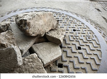 background close up broken pieces of concrete stacking on the manhole cover jumbling on the side road, element of bad managing in construction process