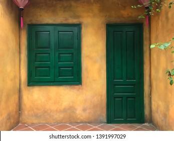Background of a closed,dark green wooden door and window of a building located in Danang, Vietnam.