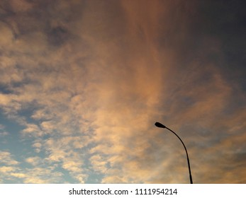 Background of cloudy sky at sunset with lonely street lamp silhouette