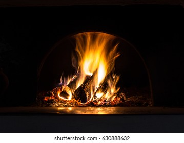 Background with coals, flame and fire at night.