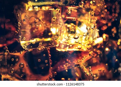 Background of cola with ice and bubbles. Side view background of refreshing cola flavored soda with carbonated with vintage tone.