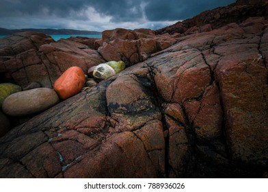 Background of colored sea stones on the shore with the dark abyss. Beautiful landscape of the Barets sea. Teriberka. Arctic. Stone resembles a human face