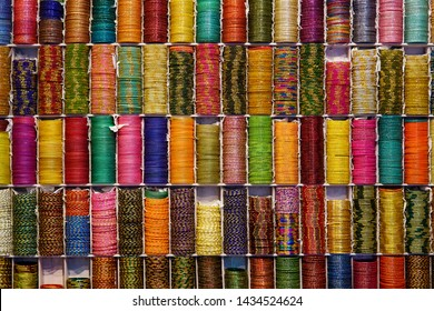 Background of colorful bangles stacked in a shop in India with glitter and plain colored bangles. The bangles are made of glass, metal or lac and worn regularly or on special occasions by Indian women - Shutterstock ID 1434524624