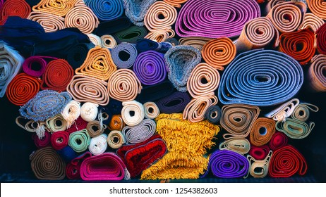 background of colorful carpets rolled and stacked