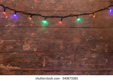 Background of colorful Christmas lights on rustic wood.