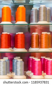 Background with a lot of colorful coils with threads. Bobbins are stacked in three rows, one on the other. The winding is erratic. Multicolored threads BANNER, vertical photo